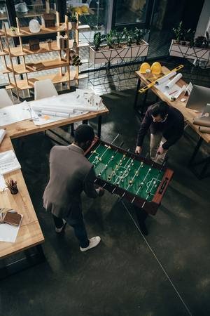 high angle view of multiethnic architects playing table football in office Stok Fotoğraf