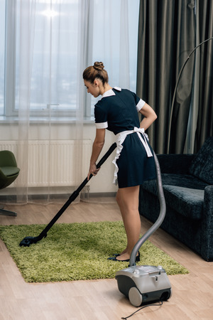 young beautiful maid in uniform using vacuum cleaner to clean carpet