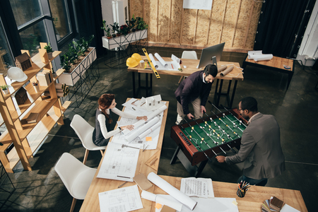 high angle view of young architects playing table football at modern office Stok Fotoğraf