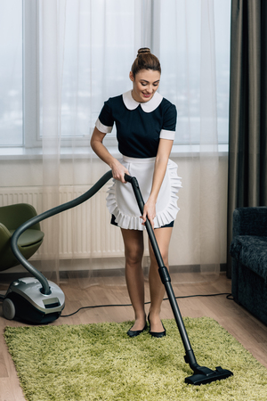 young beautiful maid in uniform using vacuum cleaner to clean carpet at hotel suite