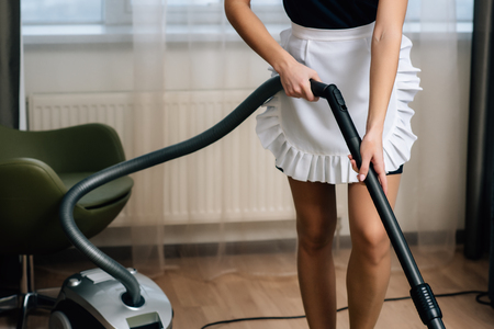 cropped shot of maid in apron using vacuum cleaner