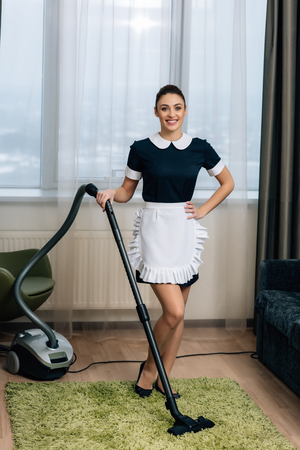 young beautiful maid in uniform standing at hotel suite with vacuum cleaner Standard-Bild - 114546663