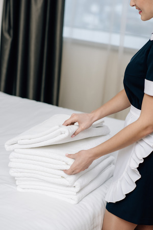 cropped shot of smiling maid in uniform with stack of clean towels on bed in hotel suite