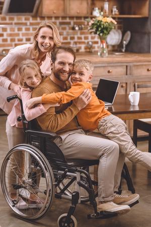 famiglia felice con due bambini e padre in sedia a rotelle che abbraccia e sorride alla macchina fotografica a casa Archivio Fotografico