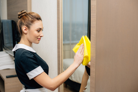 young beautiful maid in uniform cleaning mirror at hotel suit with rag