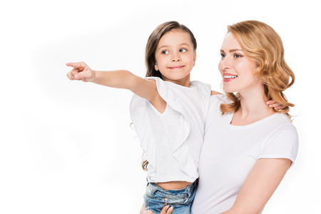 portrait of kid pointing away while showing something to mother isolated on white Imagens