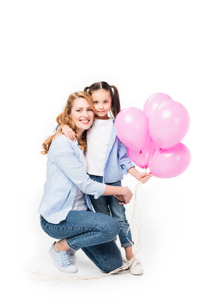 smiling mother and daughter with pink balloons hugging each other isolated on white