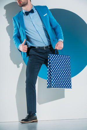 stylish young man with shopping bag stepping through hole on grey