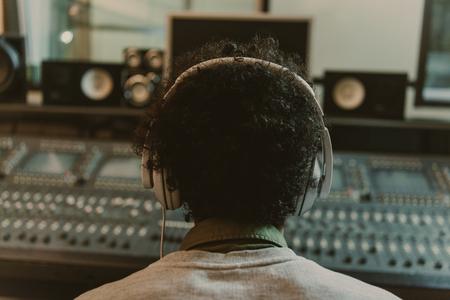 back view of sound producer in headphones sitting at studio Stock Photo - 114547800