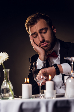 tired man looking at watch while waiting for romantic date in restaurant