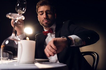 handsome bearded man looking at watch while waiting for romantic date in restaurant