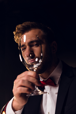 handsome bearded man looking through wine glass