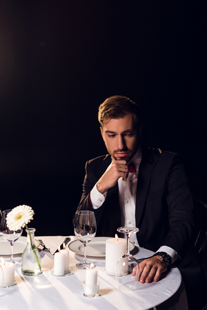 handsome bearded man in jacket waiting for romantic date in restaurant Stock Photo