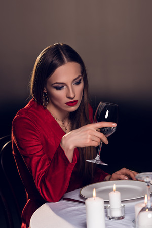 upset woman drinking wine while waiting for romantic date in restaurant