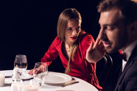 girlfriend slaping her boyfriend during romantic date in restaurant Stock Photo