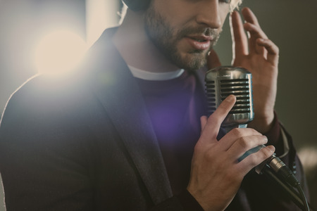 attractive young singer in headphones performing song at studio Stock Photo