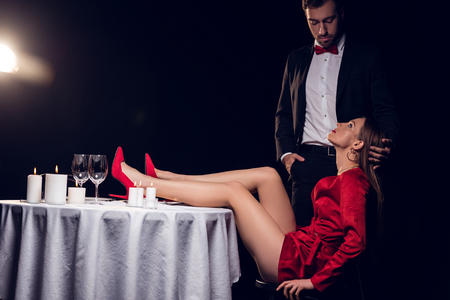 woman in red dress sitting at table with her boyfriend
