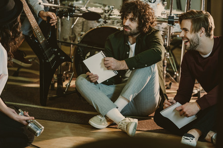 music band sitting on floor with notepads and talking