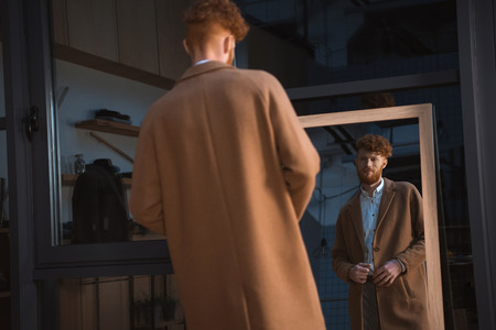 back view of young man wearing overcoat and looking at mirror in boutique