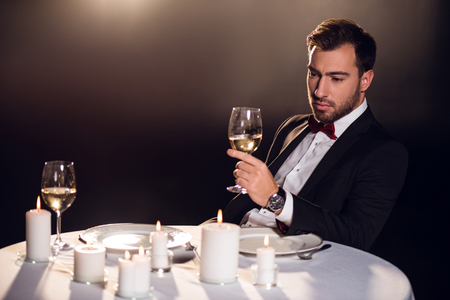 upset man drink wine while waiting for date in restaurant
