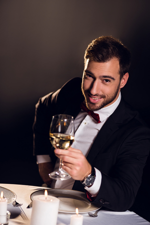 smiling bearded man with glass of wine sitting in restaurant