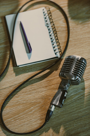 top view of wired retro microphone lying on wooden table with blank notebook 写真素材