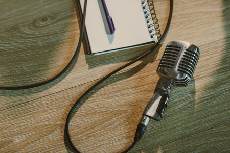 top view of wired vintage microphone lying on wooden table with blank notebook