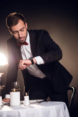 handsome man in jacket looking at watch and waiting for romantic date in restaurant Stock Photo