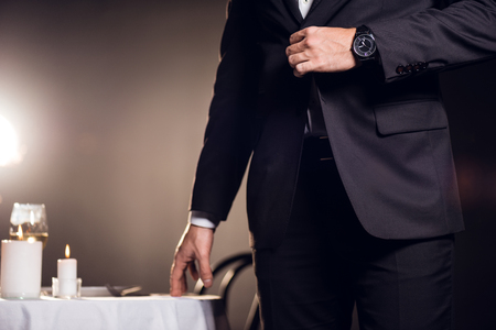 cropped view of man in jacket waiting for romantic date in restaurant