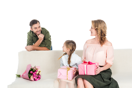 man looking at happy family with gifts on sofa isolated on white Фото со стока