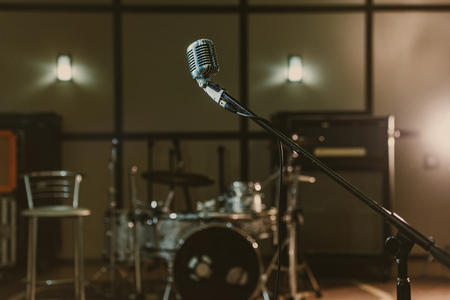 vintage microphone on stand against blurred drum set