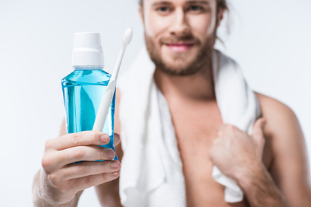 Smiling man with towel around his neck holding  tooth rinse and toothbrush in hand, isolated on white