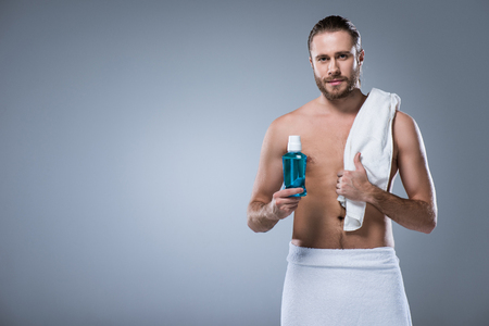 man with bath towel on shoulder holding bottle with tooth rinse in hand, isolated on gray