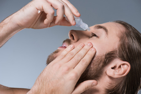 Portrait of handsome young man dripping eye drops with hand on cheek, isolated on gray Stock Photo
