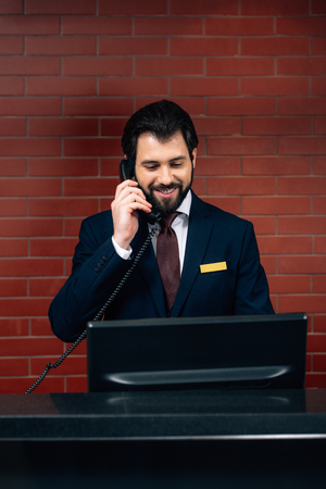 hotel receptionist taking phone call at workplace