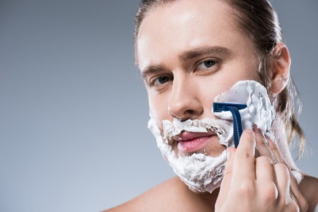 Caucasian man shaving his face with foam on his face and razor in hand, isolated on gray