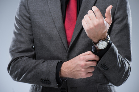 Midsection of businessman in formal suit adjusting button on sleeve, isolated on gray Banco de Imagens