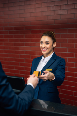 young happy hotel receptionist taking credit card from customer Standard-Bild