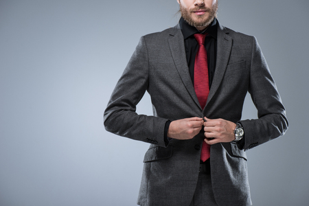 Cropped image of businessman buttoning his jacket, isolated on gray Stock Photo