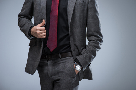 Cropped image of businessman holding side of jacket and hand in pocket, isolated on gray Stock Photo
