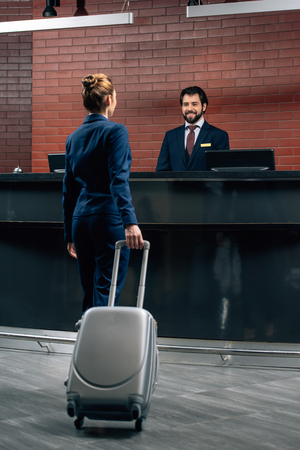 businesswoman with luggage going at hotel reception counter Stok Fotoğraf - 114548930