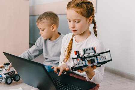 teen schoolgirl programming robot while sitting on floor with kid