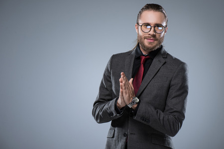 Young businessman in glasses with folded hands smiling to camera, isolated on gray Stock Photo