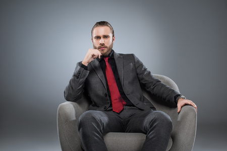 serious young businessman in formal suit sitting on armchair, with hand on chin, isolated on gray