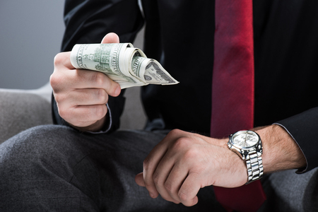 Midsection of businessman sitting in armchair  and holding money in hand, isolated on gray Stock Photo
