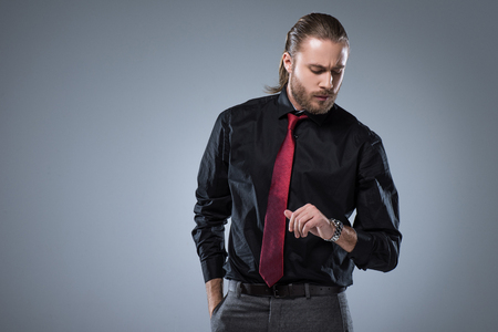Serious man in black shirt with red tie looking on wristwatch, isolated on gray 版權商用圖片