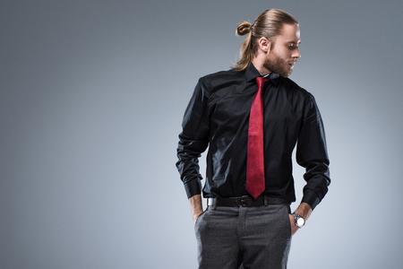 Jeune homme barbu en chemise noire avec cravate rouge à l'écart, isolé sur gris