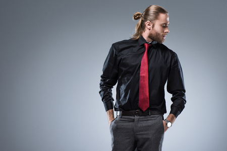 Young bearded man in black shirt with red tie looking away, isolated on gray