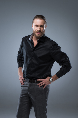 Handsome young man in black shirt looking at camera with hands on waist , isolated on gray