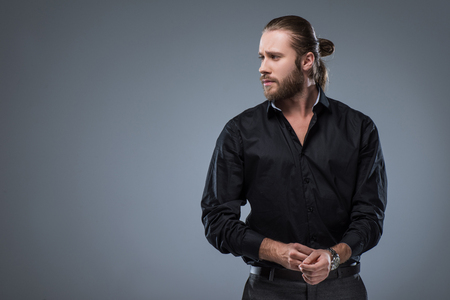Handsome bearded man in black shirt looking away, isolated on gray